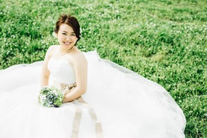 bride sits on grass and shows us big smile