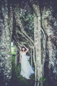 Bride stands by tree